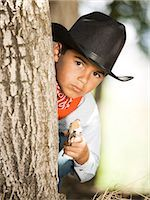Boy in cowboy costume with toy gun Stock Photo - Premium Royalty-Freenull, Code: 640-03259358