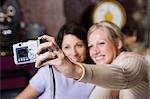 Two girl friends using a digital camera Stock Photo - Premium Royalty-Free, Artist: Dave Robertson, Code: 640-03259440