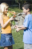 Boy giving girl flowers Stock Photo - Premium Royalty-Freenull, Code: 640-03261020