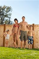 Family in bathing suits holding hands in yard Stock Photo - Premium Royalty-Freenull, Code: 640-03262819