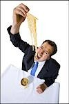 Businessman awkwardly eating noodles Stock Photo - Premium Royalty-Free, Artist: Masterfile, Code: 640-03265127