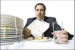Overweight businessman gorging himself on spaghetti Stock Photo - Premium Royalty-Free, Artist: Masterfile, Code: 640-03265133