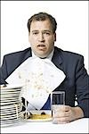 Overweight businessman gorging himself on spaghetti Stock Photo - Premium Royalty-Free, Artist: Masterfile, Code: 640-03265135