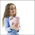 Young girl hugging piggy bank Stock Photo - Premium Royalty-Freenull, Code: 640-03265240