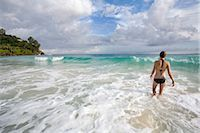 Young woman walking into ocean, Seychelles Stock Photo - Premium Royalty-Freenull, Code: 682-03285646