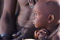 shy baby - Profile view of a Himba child and torso of man, Van Zyl's Pass area, Kaokoland, Namibia Stock Photo - Premium Royalty-Freenull, Code: 682-03285693