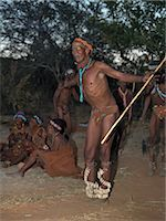 A Bushman,or San,mimics an ostrich as he sings and dances round a campfire. The rest if the band keeps rhythm to the noise of the rattles wound round the dancer's legs. These NS hunter gatherers live in the Xai Xai Hills close to the Namibian border. Their traditional way of life is fast disappearing. Stock Photo - Premium Rights-Managednull, Code: 862-03289587
