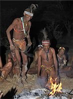 A bushman,or San,collapses in a trance during a sing-song round their campfire. The men have rattles wound round their legs to help the rest of them keep rhythm during their dances.These NS hunter gatherers live in the Xai Xai Hills close to the Namibian border. Their traditional way of life is fast disappearing. Stock Photo - Premium Rights-Managednull, Code: 862-03289590