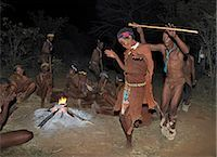 A man and wife of a San community dance during a sing-song round their campfire. The men have rattles wound round their legs to help the rest of them keep rhythm during their dances.These NS hunter gatherers live in the Xai Xai Hills close to the Namibian border. Their traditional way of life is fast disappearing. Stock Photo - Premium Rights-Managednull, Code: 862-03289593