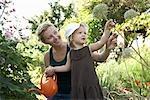 Mother and Daughter in Garden Watering Plants