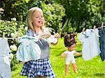 Girl spreading out her doll clothes Stock Photo - Premium Royalty-Freenull, Code: 649-03296425