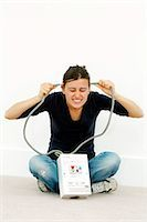 Woman joking while doing DIY. She is holding the cables to a high-voltage mains box to her head. Stock Photo - Premium Royalty-Freenull, Code: 679-03298382