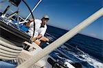 Sailor at helm of yacht on ocean Stock Photo - Premium Royalty-Free, Artist: Westend61, Code: 693-03299359