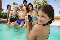 seniors woman in swimsuit - Girl (10-12) in swimming pool, video taping brother (13-15), parents, and grandparents, portrait. Stock Photo - Premium Royalty-Freenull, Code: 693-03299419