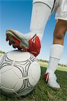 Soccer player (13-17) standing on ball, low section Stock Photo - Premium Royalty-Freenull, Code: 693-03299561