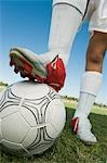 Soccer player (13-17) standing on ball, low section Stock Photo - Premium Royalty-Free, Artist: Masterfile, Code: 693-03299561