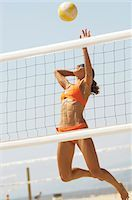 spike - Female beach volleyball player jumping to spike volleyball over net Stock Photo - Premium Royalty-Freenull, Code: 693-03299660