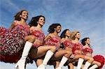 Cheerleaders in a row kicking legs