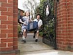 Elementary students running out through school gate Stock Photo - Premium Royalty-Free, Artist: AWL Images, Code: 693-03300829