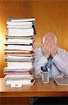 Businessman covering face with hands next to stack of paperwork at desk Stock Photo - Premium Royalty-Free, Artist: Anna Huber, Code: 693-03301339