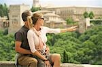 Tourist Couple sitting on Wall in Granada, Spain, looking and pointing at view Stock Photo - Premium Royalty-Free, Artist: AWL Images, Code: 693-03301529