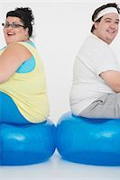 fat man exercising - Overweight man and woman sitting back to back on exercise balls, portrait Stock Photo - Premium Royalty-Freenull, Code: 693-03302952