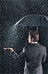 Businessman sticking hand out from under umbrella to feel rain, back view Stock Photo - Premium Royalty-Free, Artist: Mishchenko                    , Code: 693-03303403