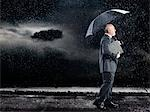 Businessman Walking in rain under umbrella, side view Stock Photo - Premium Royalty-Free, Artist: FotoVika                      , Code: 693-03303424