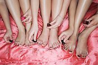 Teenage girls painting toenails on pink sheets, high angle view, close-up Stock Photo - Premium Royalty-Freenull, Code: 693-03303562