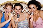 Teenage Girls using brushes as microphones, singing at  Slumber Party