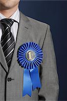 Man wearing blue ribbon on lapel against dark background, mid section Stock Photo - Premium Royalty-Freenull, Code: 693-03303791