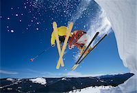 Skiers launching off snow bank, Hitting the Slopes, low angle view Stock Photo - Premium Royalty-Freenull, Code: 693-03303821