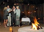 Four people toasting at outdoor nightclub near bonfire, night Stock Photo - Premium Royalty-Free, Artist: Bettina Salomon, Code: 693-03304079