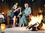 Two women sitting by bonfire at outdoor nightclub, toasting Stock Photo - Premium Royalty-Free, Artist: photo division           , Code: 693-03304082