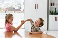 superior - Young girl and boy fighting at table at home Stock Photo - Premium Royalty-Freenull, Code: 693-03304591