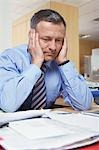Businessman sitting at desk with head in hands Stock Photo - Premium Royalty-Free, Artist: Russell Monk, Code: 693-03305037