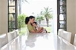 Mother and daughter (5-6 years) embracing, sitting at dining table Stock Photo - Premium Royalty-Free, Artist: AWL Images, Code: 693-03305703