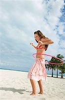 Teenage girl (16-17) playing with hoola hoop on beach Stock Photo - Premium Royalty-Freenull, Code: 693-03305805
