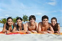 Group of teenagers (16-17) lying in row on beach towels, portrait Stock Photo - Premium Royalty-Freenull, Code: 693-03305814