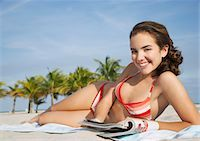 Teenage girl (16-17) reading magazine, lying on beach, portrait Stock Photo - Premium Royalty-Freenull, Code: 693-03305818