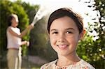 Girl smiling, head and shoulders, mother watering garden Stock Photo - Premium Royalty-Free, Artist: Westend61, Code: 693-03306067