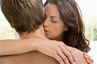 Woman kissing man's neck, head and shoulders Stock Photo - Premium Royalty-Freenull, Code: 693-03306183