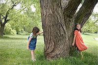 Two girls (7-9) playing hide and seek by tree Stock Photo - Premium Royalty-Freenull, Code: 693-03306970