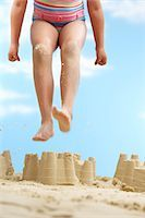 preteen girl feet - Girl (7-9 years) jumping on sand castle on beach, low section Stock Photo - Premium Royalty-Freenull, Code: 693-03307024