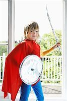 Portrait of young boy (7-9) in superhero costume holding toy shield and sword, smiling Stock Photo - Premium Royalty-Freenull, Code: 693-03307199