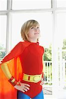 Portrait of young boy (7-9) in superhero costume, hands on hip, indoors Stock Photo - Premium Royalty-Freenull, Code: 693-03307202