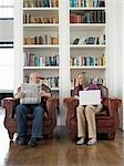 Couple sitting in armchairs, man reading newspaper, woman using laptop Stock Photo - Premium Royalty-Freenull, Code: 693-03307610