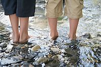 Two boys (7-9, 10-12) standing in stream, low section, back view Stock Photo - Premium Royalty-Freenull, Code: 693-03307988