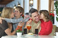 preteen kissing - Parents and children (7-9) with drinks, embracing at restaurant Stock Photo - Premium Royalty-Freenull, Code: 693-03309580