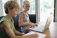 Siblings (6-8) sitting at table doing homework with laptop Stock Photo - Premium Royalty-Freenull, Code: 693-03309627